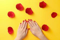 Femme tenant des mains près des pétales de rose sur le fond de couleur Beau vernis ? ongles photo stock
