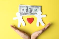 Femme tenant des mains près des silhouettes de papier des factures de personnes, de coeur et d'argent sur le fond de couleur, vue image stock