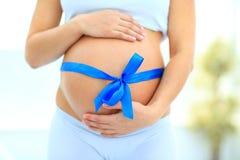 Femme tenant des mains sur sa bosse de bébé Photo stock