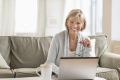 Femme tenant des verres tout en à l'aide de l'ordinateur portable dans le salon Images libres de droits