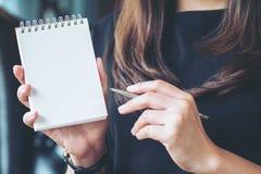 Femme tenant et montrant le carnet vide dans le bureau Images stock