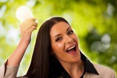 Femme tenant l'ampoule au-dessus de la tête comme signe de nouvelle idée Photographie stock