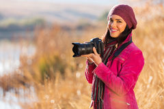 Femme tenant l'appareil-photo de dslr Photo stock