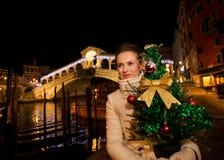 Femme tenant l'arbre de Noël près du pont de Rialto à Venise, Italie Photographie stock