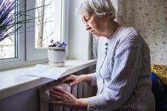 Femme tenant l'argent liquide devant le radiateur de chauffage Paiement pour chauffer en hiver Foyer sélectif images libres de droits