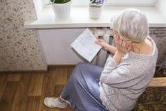 Femme tenant l'argent liquide devant le radiateur de chauffage Paiement pour chauffer en hiver Foyer sélectif photos libres de droits