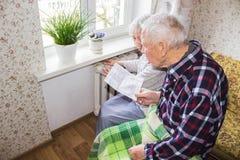 Femme tenant l'argent liquide devant le radiateur de chauffage Paiement pour chauffer en hiver Foyer sélectif image libre de droits