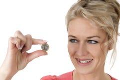 Femme tenant l'euro pièce de monnaie entre deux doigts photographie stock
