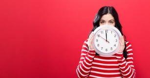 Femme tenant l'horloge montrant presque 12 Photo stock
