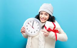 Femme tenant l'horloge montrant presque 12 Photographie stock libre de droits