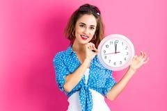 Femme tenant l'horloge montrant presque 12 Images stock