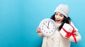 Femme tenant l'horloge montrant presque 12 Photographie stock