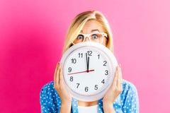 Femme tenant l'horloge montrant presque 12 Photos stock