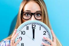 Femme tenant l'horloge montrant presque 12 Photo libre de droits
