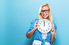 Femme tenant l'horloge montrant presque 12 Image stock