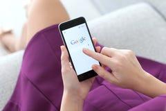 Femme tenant l'iPhone 6 avec le service Google sur l'écran Image stock