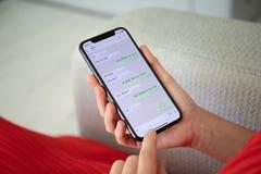 Femme tenant l'iPhone X avec le service social WhatsApp de mise en réseau photographie stock libre de droits
