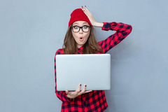 Femme tenant l'ordinateur portable et regardant l'appareil-photo Images libres de droits