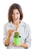 Femme tenant l'usine de cactus et poignardée son doigt avec f douloureux Photographie stock