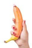 Femme tenant la banane avec le préservatif d'isolement sur le fond blanc Main de femme de sexe de satisfaction de préservatif de  Image stock