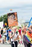 Femme tenant la bannière dans la foule pendant Stockholm Pride Parade Photographie stock libre de droits