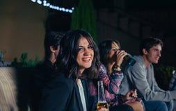 Femme tenant la bière et ses amis parlant en partie Photographie stock libre de droits
