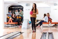 Femme tenant la boule dans le bowling Images stock