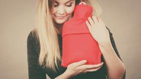Femme tenant la bouteille d'eau d'un rouge ardent chaude photo libre de droits