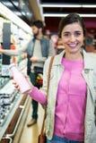 Femme tenant la bouteille et le sourire à lait Images stock