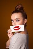 femme tenant la carte avec la marque de rouge à lèvres de baiser sur le fond de gradient Photographie stock libre de droits