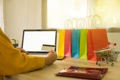 Femme tenant la carte de crédit et à l'aide de l'ordinateur portable pour faire des emplettes en ligne images libres de droits