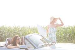 Femme tenant la carte tandis qu'ami s'asseyant dans le convertible contre le ciel clair le jour ensoleillé Image stock