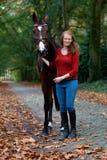 Femme tenant la forêt noire de ruelle d'avenue de cheval d'étalon photos libres de droits