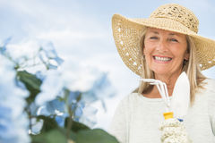 Femme tenant la fourchette et la truelle de jardinage contre le ciel Photos libres de droits