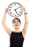 Femme tenant la grande horloge Image libre de droits
