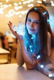 Femme tenant la guirlande rougeoyante de Noël dans des mains Images stock