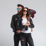 Femme tenant la guitare électrique sur l'épaule avec l'homme derrière elle Images libres de droits