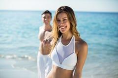 Femme tenant la main d'ami sur le rivage à la plage Photos libres de droits