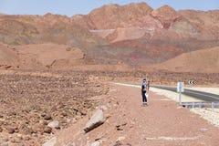 Femme tenant la route proche de désert d'asphalte Photo stock