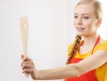 Femme tenant la spatule en bois de cuisine avec le coeur Image stock