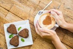 Femme tenant la tasse chaude du gâteau de café et de chocolat dans la forme Photos libres de droits