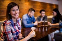 Femme tenant la tasse de bière avec des amis à l'arrière-plan Image stock