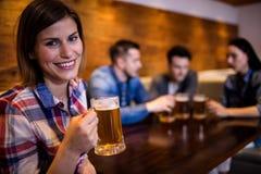 Femme tenant la tasse de bière tandis qu'amis à l'arrière-plan Photo stock