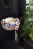 Femme tenant la tasse de café avec les clous rouges Image stock