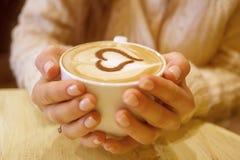Femme tenant la tasse de café chaude Images stock