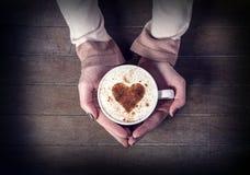 Femme tenant la tasse de café chaude, avec la forme de coeur Images libres de droits