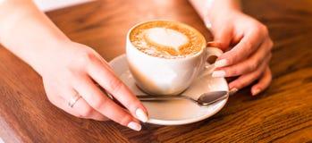 Femme tenant la tasse de café chaude, avec la forme de coeur Images stock