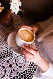 Femme tenant la tasse de café chaude Une fille en café avec les clous beiges tient une tasse avec le cappuccino avec un modèle Photo libre de droits