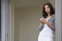 Femme tenant la tasse de café en porte Images stock