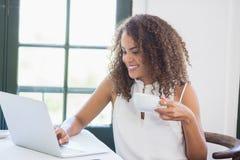Femme tenant la tasse de café et à l'aide de l'ordinateur portable dans un restaurant Photos libres de droits